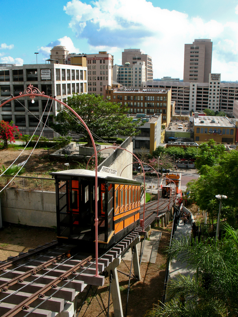 An Angels Flight car on the tracks with some of the surrounding area in the background