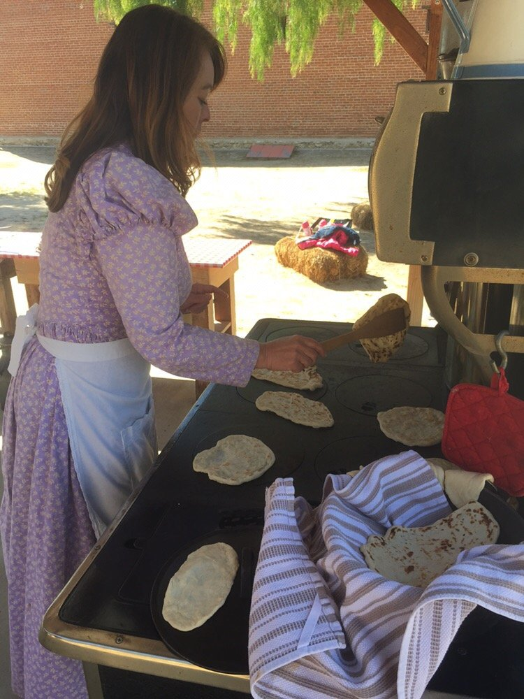 An interpreter makes tortillas for visitors