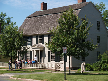 A side view of the Joseph Webb House. The two-story home features white siding and black shutters. A narrow porch runs along the front of the house. A small tree obstructs part of the view of the house.