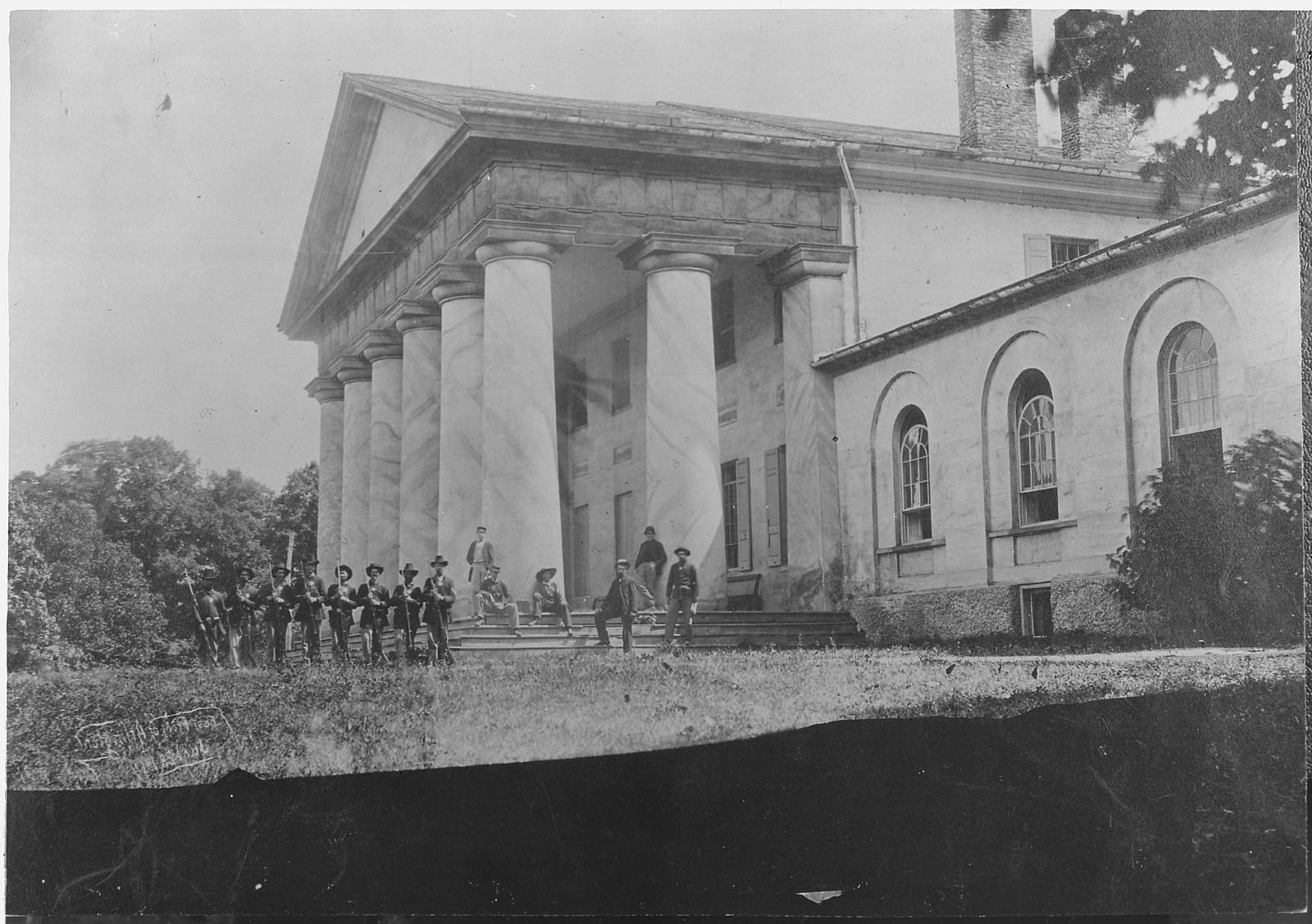 Arlington House came under Union occupation beginning in May 1861. In this image from 1864, Union soldiers pose on the grand front porch of the mansion. National Archives.
