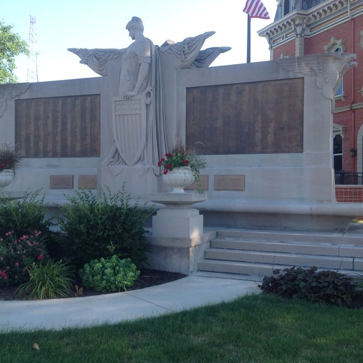 The front of the Peace Monument. Female peace standing in the center, and the bronze panels located on the left and right with the veterans names.