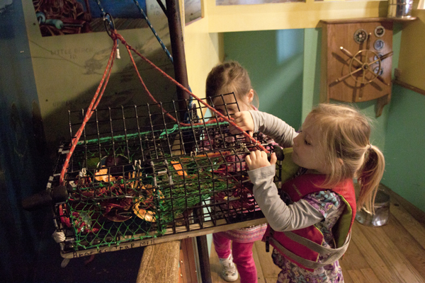 Children Explore a Lobster Trap in the Lobster Boat Exhibit that explores Maine's waterfront history.
