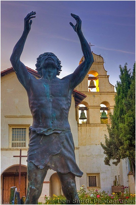 A statue of San Juan Bautista's namesake, St. John the Baptist, in front of the mission.