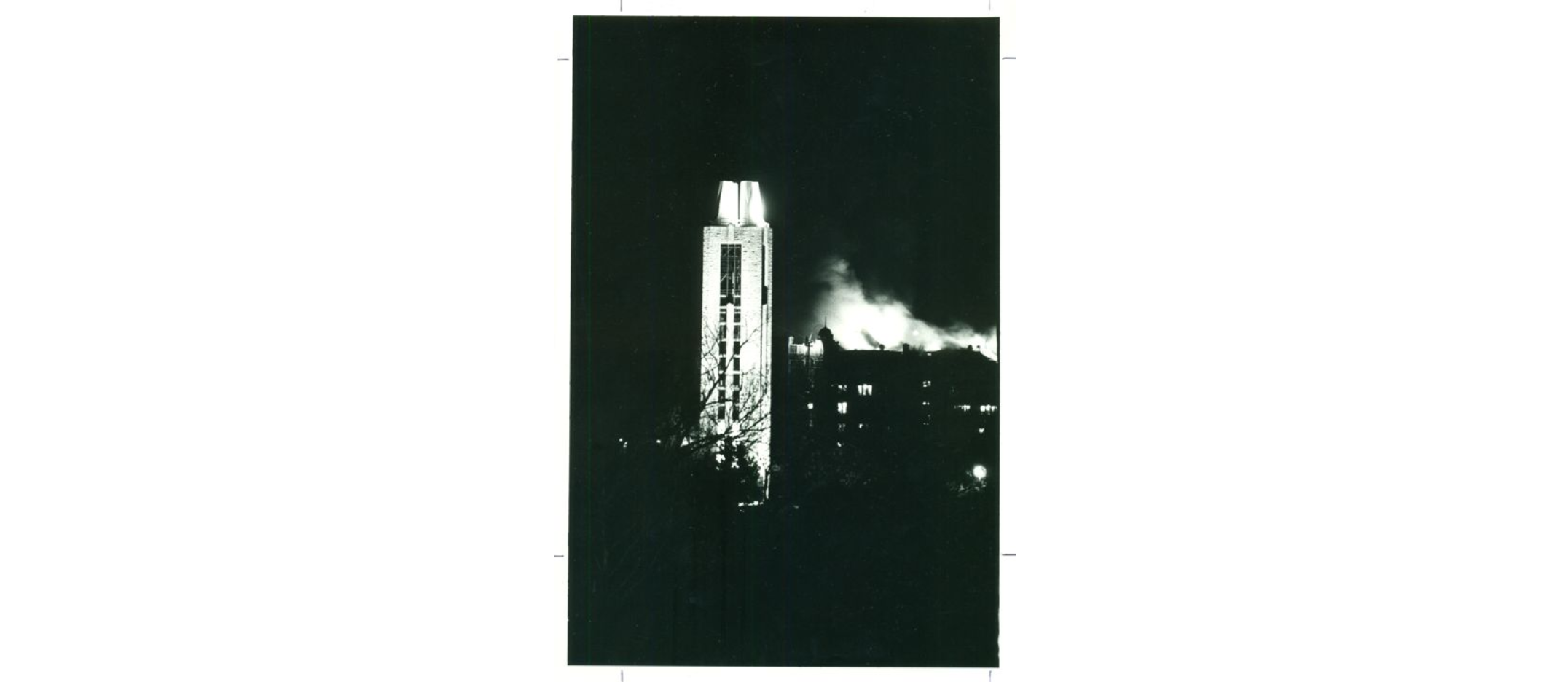 The Campanile stands in the foreground of the photograph while smoke and flames rise from the Union in the background.