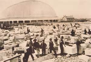 1870-1880s photo of men continuing to work on the Salt Lake City temple. The newly finished tabernacle sites in background