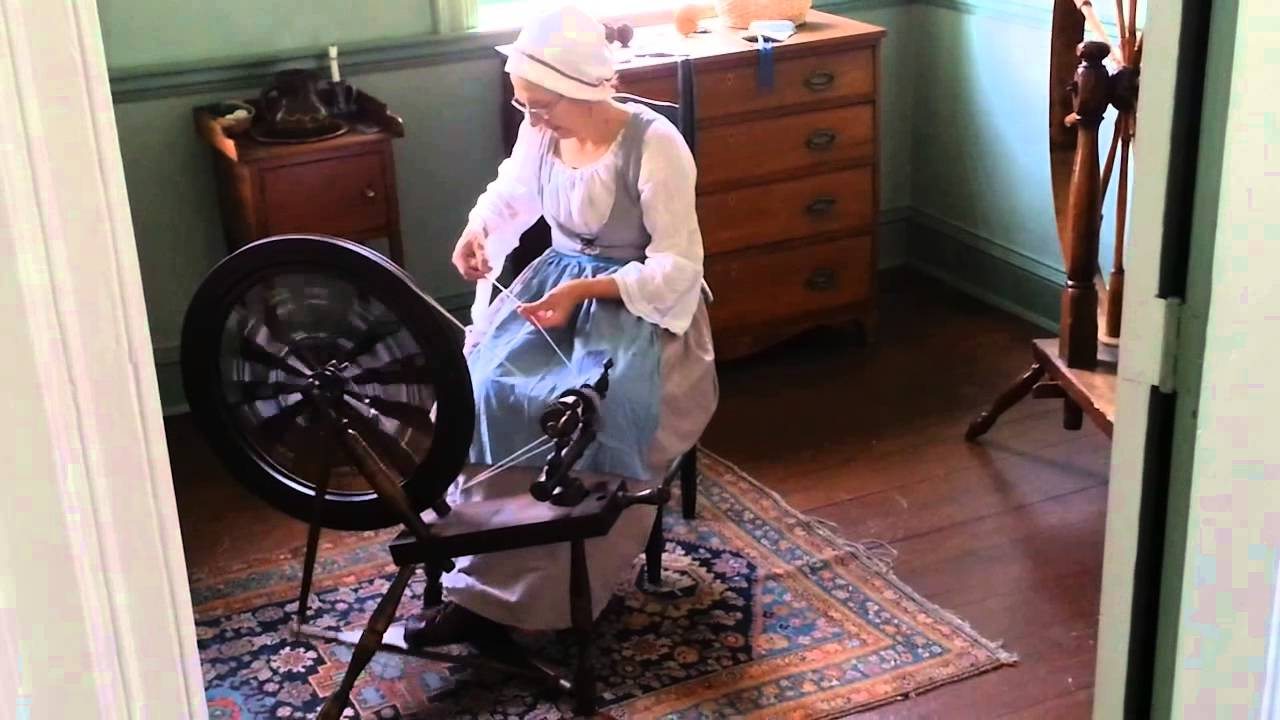 Docent demonstrating the proper use of a spinning wheel in the upstairs parlor.