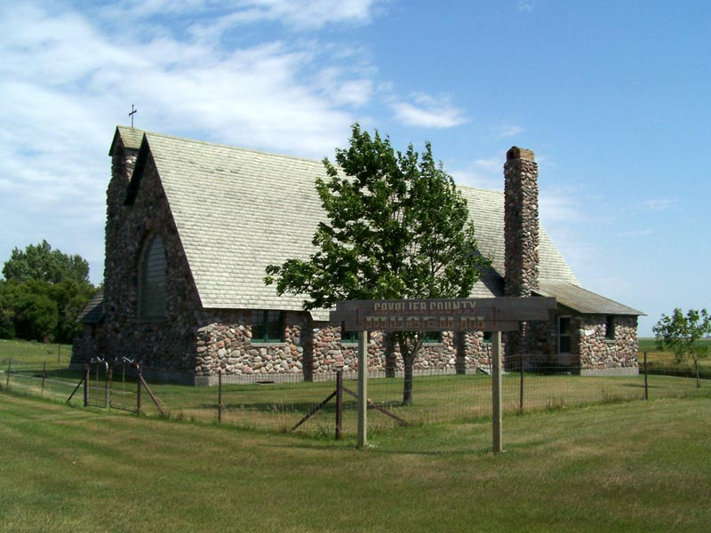 This stone building was the home of a Catholic Parish between 1936 and 1969, when the Cavalier County Historical Society acquired the building and used it to house their museum.