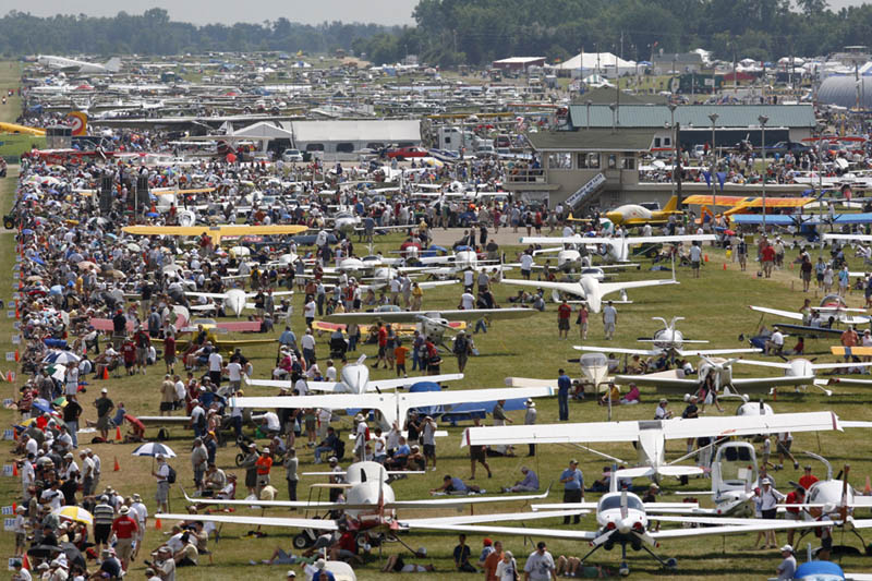 Crowds stroll through the grounds where aircraft are parked.