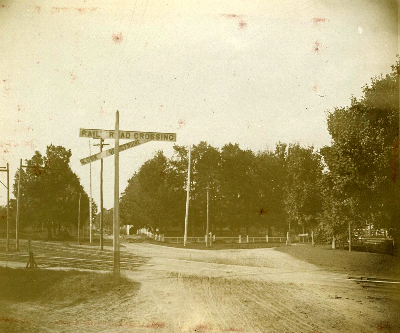 Photograph of railroad tracks and crossing.  In the background is Perkins Manor (partially obscured by trees).