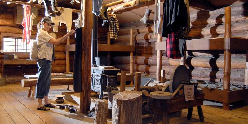 A visitor looks over some of the logging artifacts at the museum.