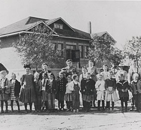Expanded schoolhouse with students and teacher in 1910