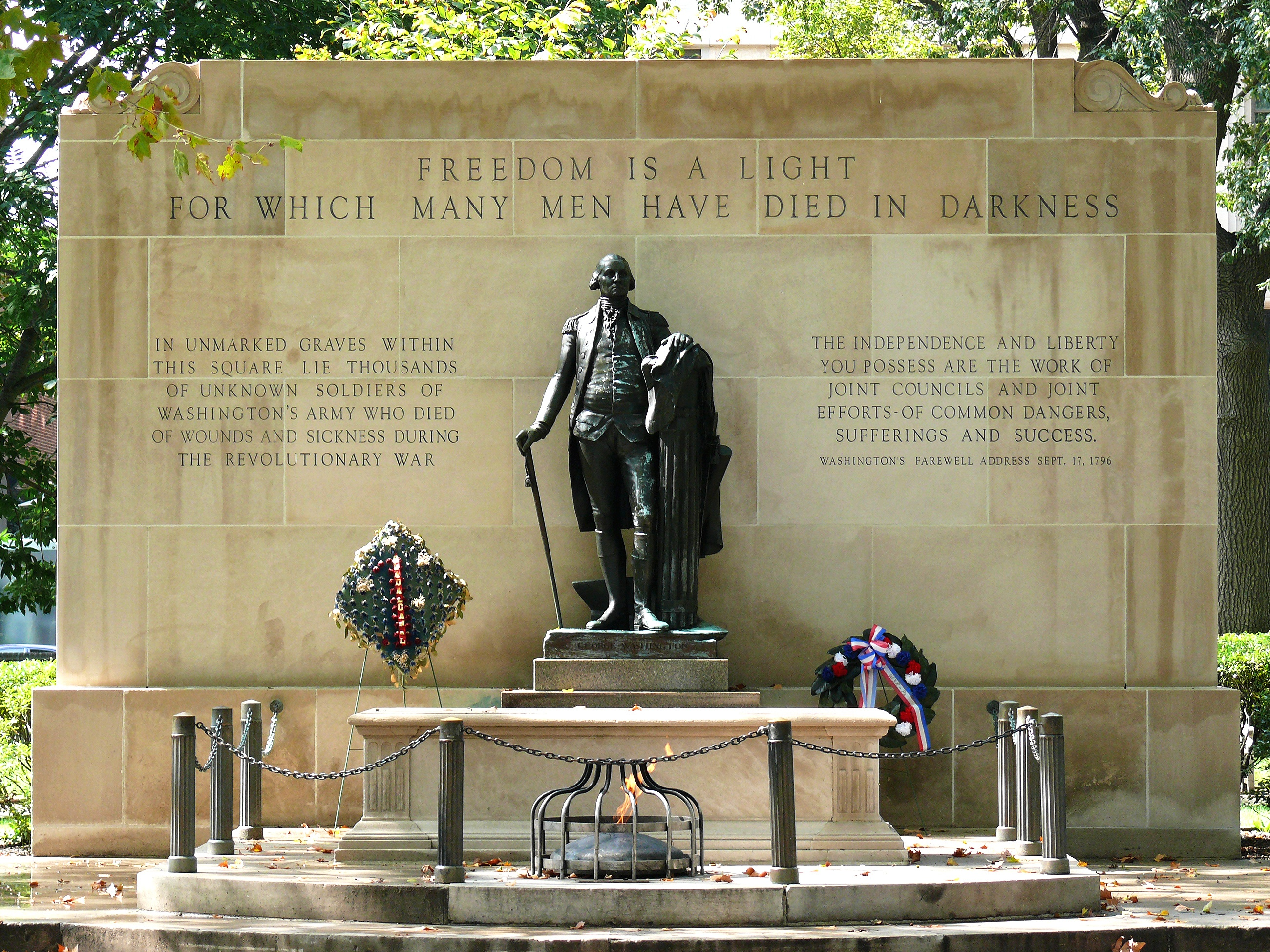 Standing over the tomb in a guardian-like pose is a bronze statue of George Washington.