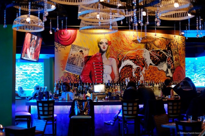 The full bar available to customers in front of one of two beautiful murals inside the restaurant.