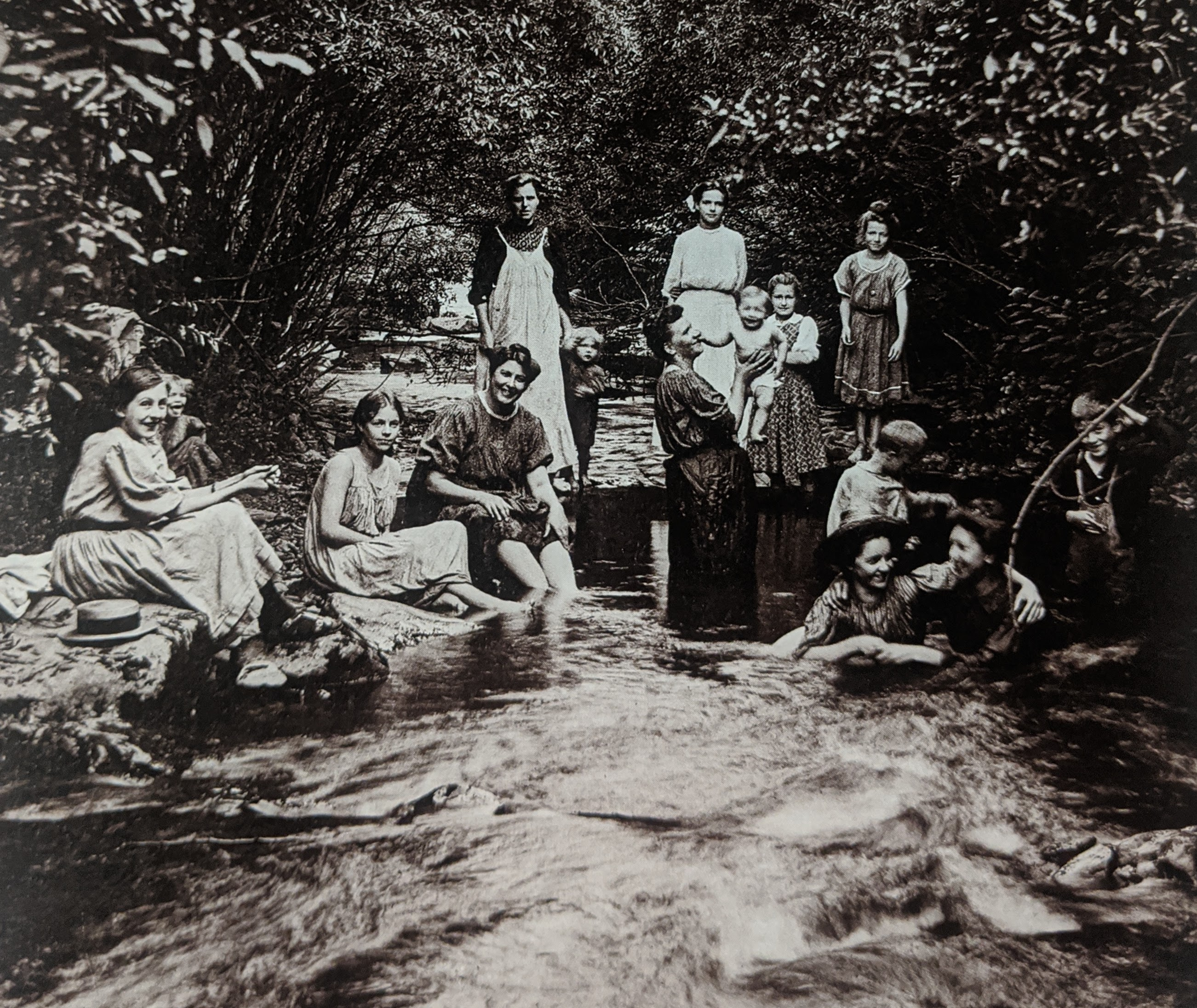 Photo taken by William T. Clarke. Women and children cooling off in creek on a hot day.