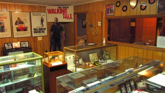 "A view inside the house, with posters of the ""Walking Tall"" movies, including the one starring ""The Rock"""