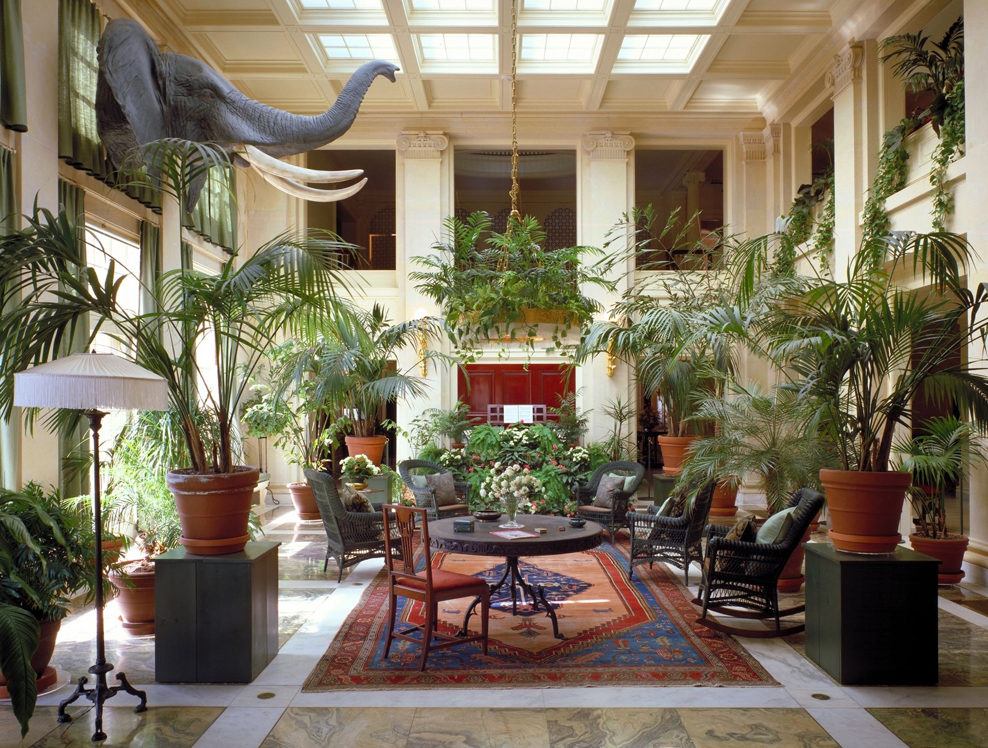 The conservatory is two stories tall and features ceiling windows and numerous plants.