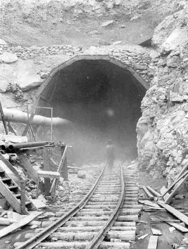 The entrance to the mine. The prodigious amount of dust raised from the tunnel's construction, clearly seen in the photograph, contained fatal amounts of silica.