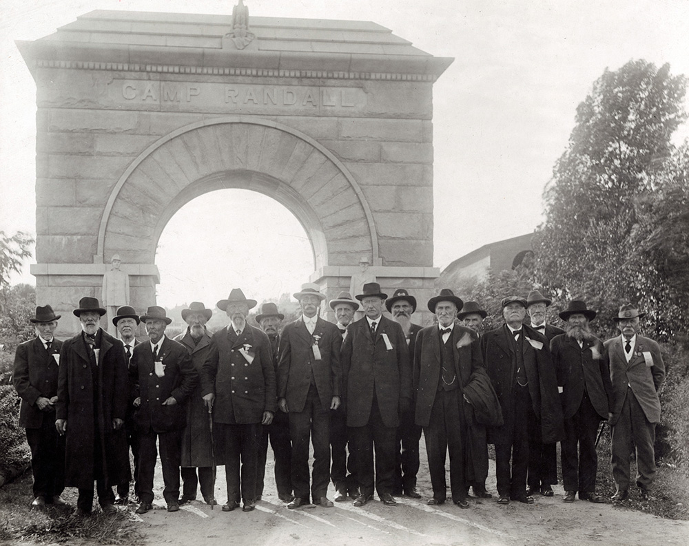 Group portrait photograph of Civil War Veterans standing in front of the Camp Randall Memorial Arch, located in Madison, Wisconsin The veterans are dressed in civilian suits, wearing ribbons and badges, likely from the Grand Army of the Republic.