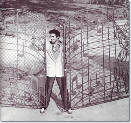 Elvis standing at the music gate that was custom designed and built for him. The gate was installed in 1957 shortly after Elvis moved into the home.