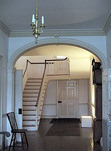 Photo of the main staircase foyer which demonstrates a distinctive slant at the top of the stairway.  Due to a lack of skilled labor there are numerous examples of craftsmanship errors throughout the house.