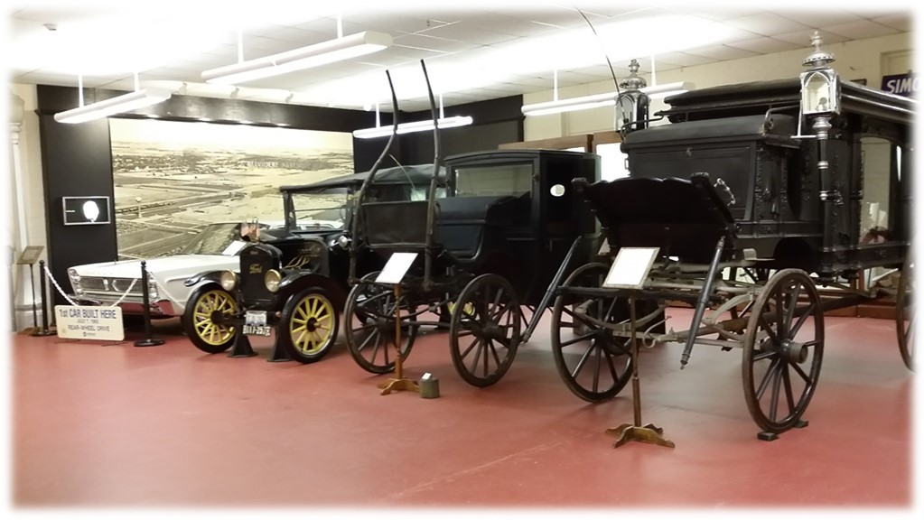 Transportation Gallery- A hand-carved hearse, horse-drawn carriage, and the first car off of the Belvidere Chrysler Plant assembly line!