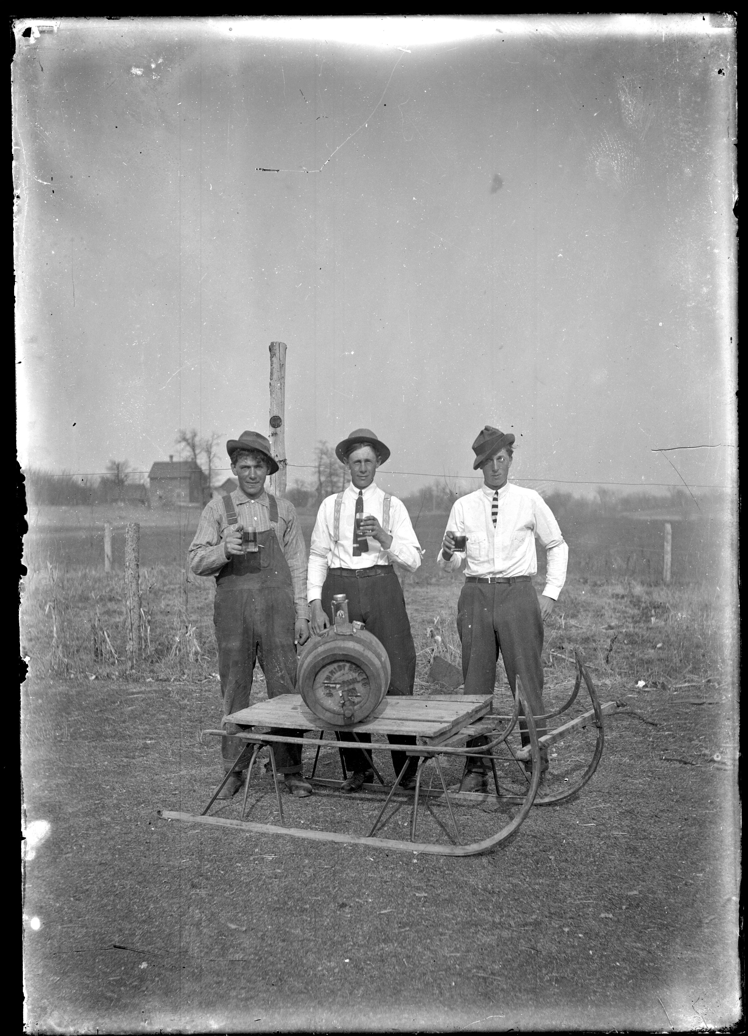 From our collection: three young men, outdoors, each with a mug of beer in their hand. They are behind a sled on which a wooden keg of beer is sitting.