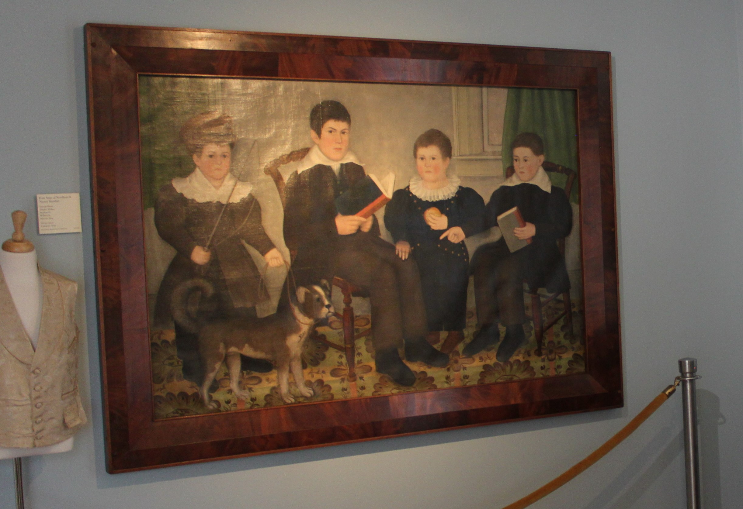 Portrait of Four Boys (American, First Half 19th Century) Unsigned. Two boys are holding books, one is holding an apple and one is holding a riding crop and standing by a dog. The background is a parlor with a patterned rug on the floor. The boys are purportedly George Henry, Charles Wilbor, Stephan H., William E. and Fido the Dog (the name of the dog is painted on the dog in the painting); the boys are the sons of Needham and Naomi Standart.