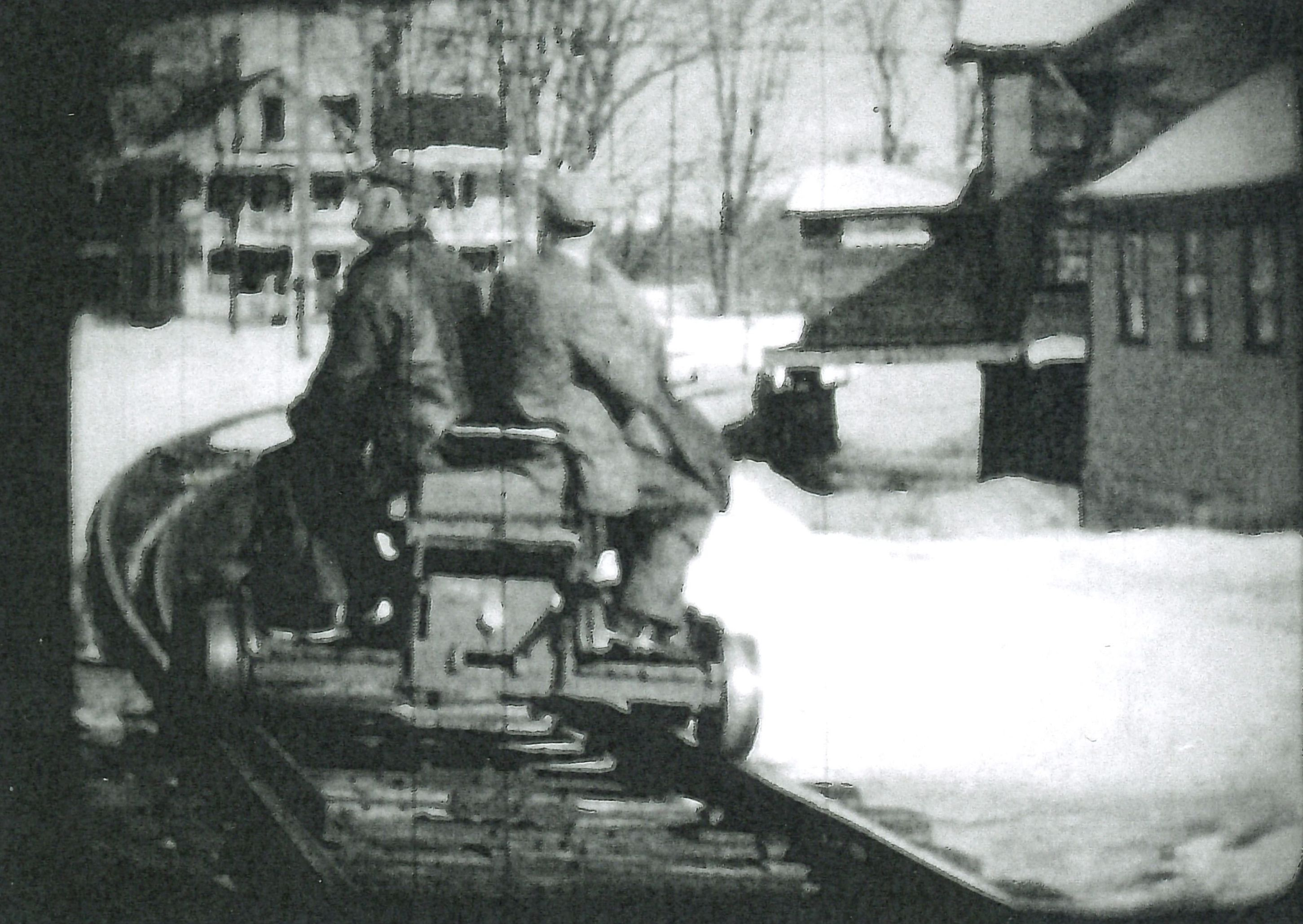 Phil Ball and Irving Hicks rounding the curve of the railroad on a hand car with the Nelson Grain Mill on the right.  From film by Oscar Polhemus, circa 1930