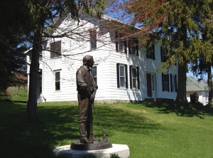 Side shot of home with statue to Joseph Smith to mark his 3-week employment under Stowell and his living in the home for a brief time with Emma