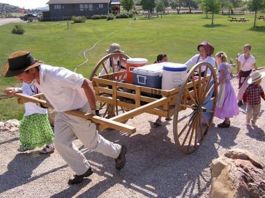 People taking part in a trek in portion of the site, trying to reenact how Mormon Pioneers traveled over 1000 miles west