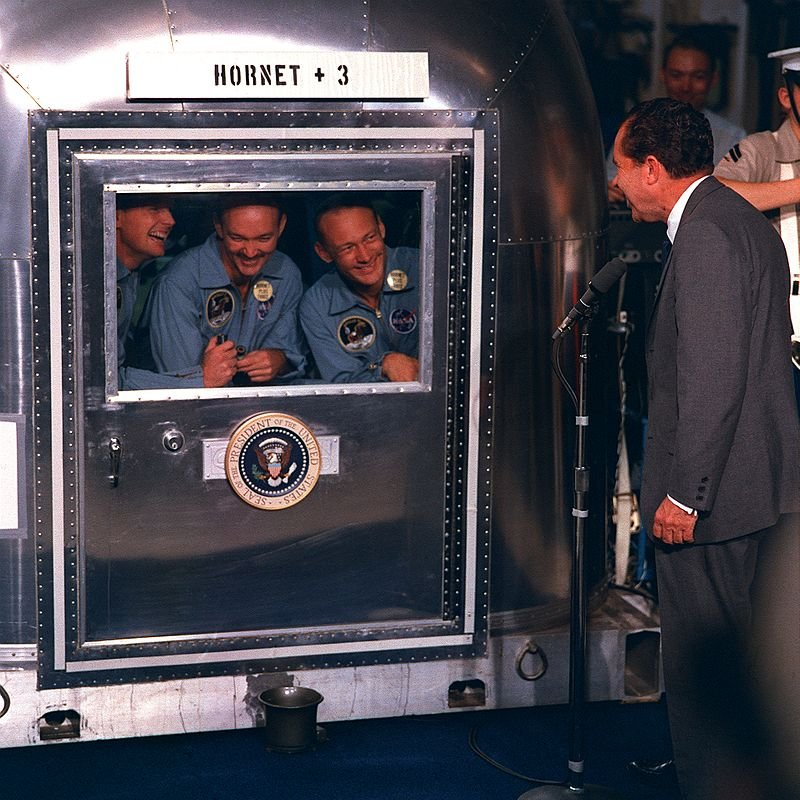President Richard Nixon greets the Apollo 11 astronauts during their quarantine aboard USS Hornet after their successful return from the moon. Left to right: Neil Armstrong, Michael Collins, and Buzz Aldrin.