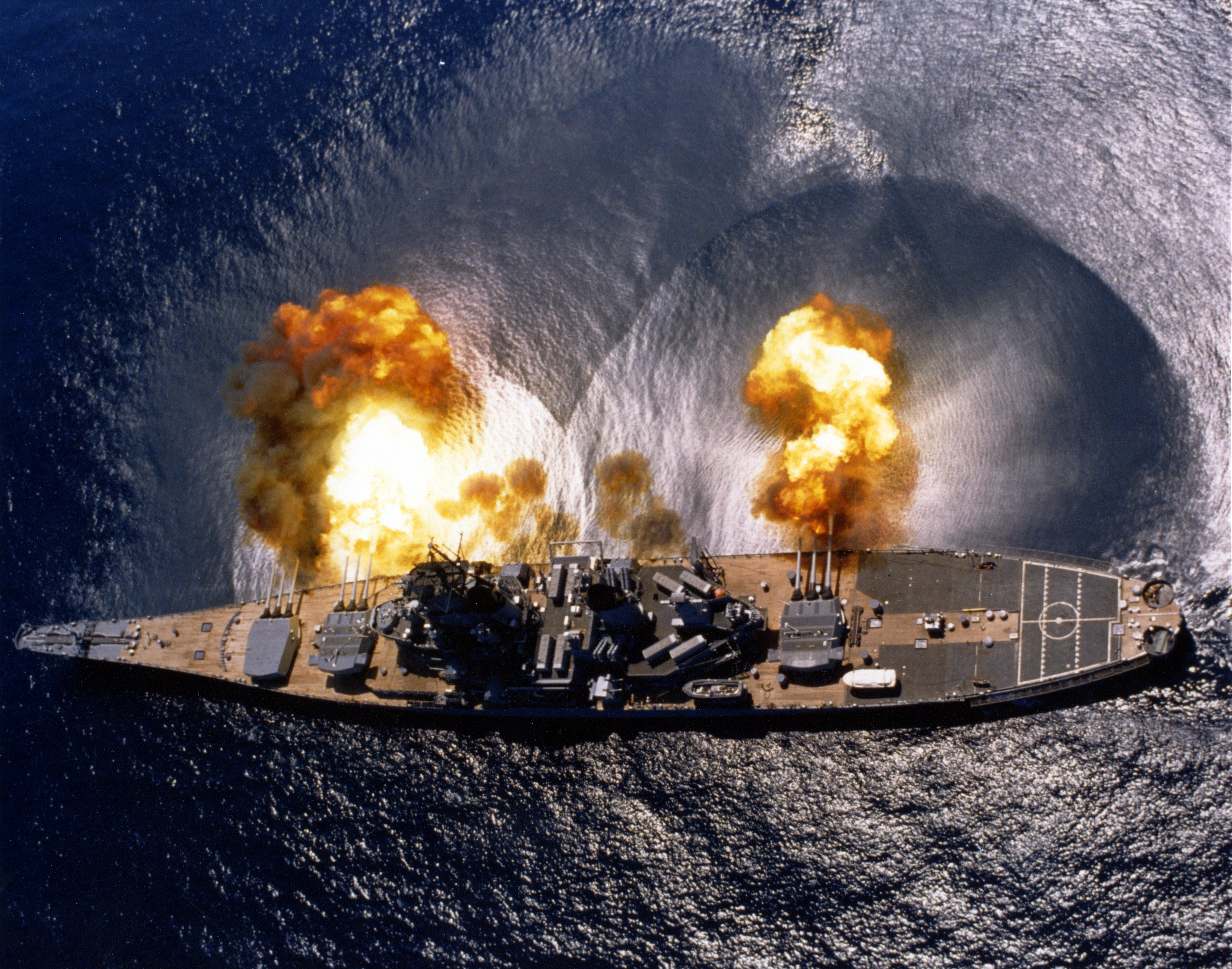 Aerial view of USS Iowa firing her main guns.  Note the shockwave visible on the water.