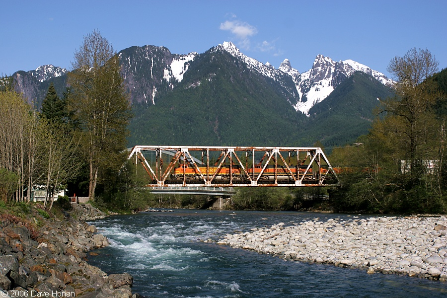 A train passes over the Skycomish River under the Cascade Mountains in Index Washington.