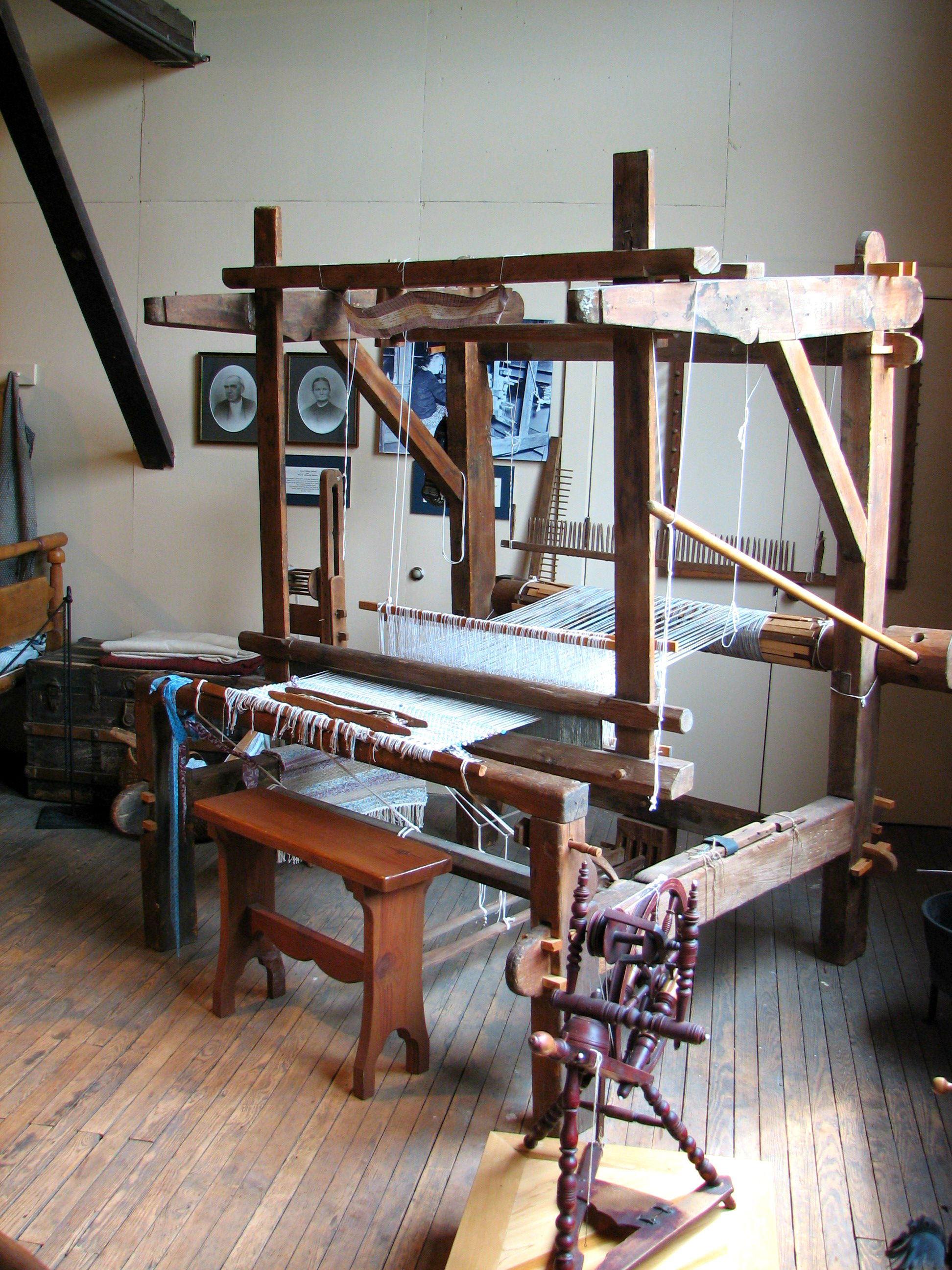 Vintage hand loom and small spinning wheel on display