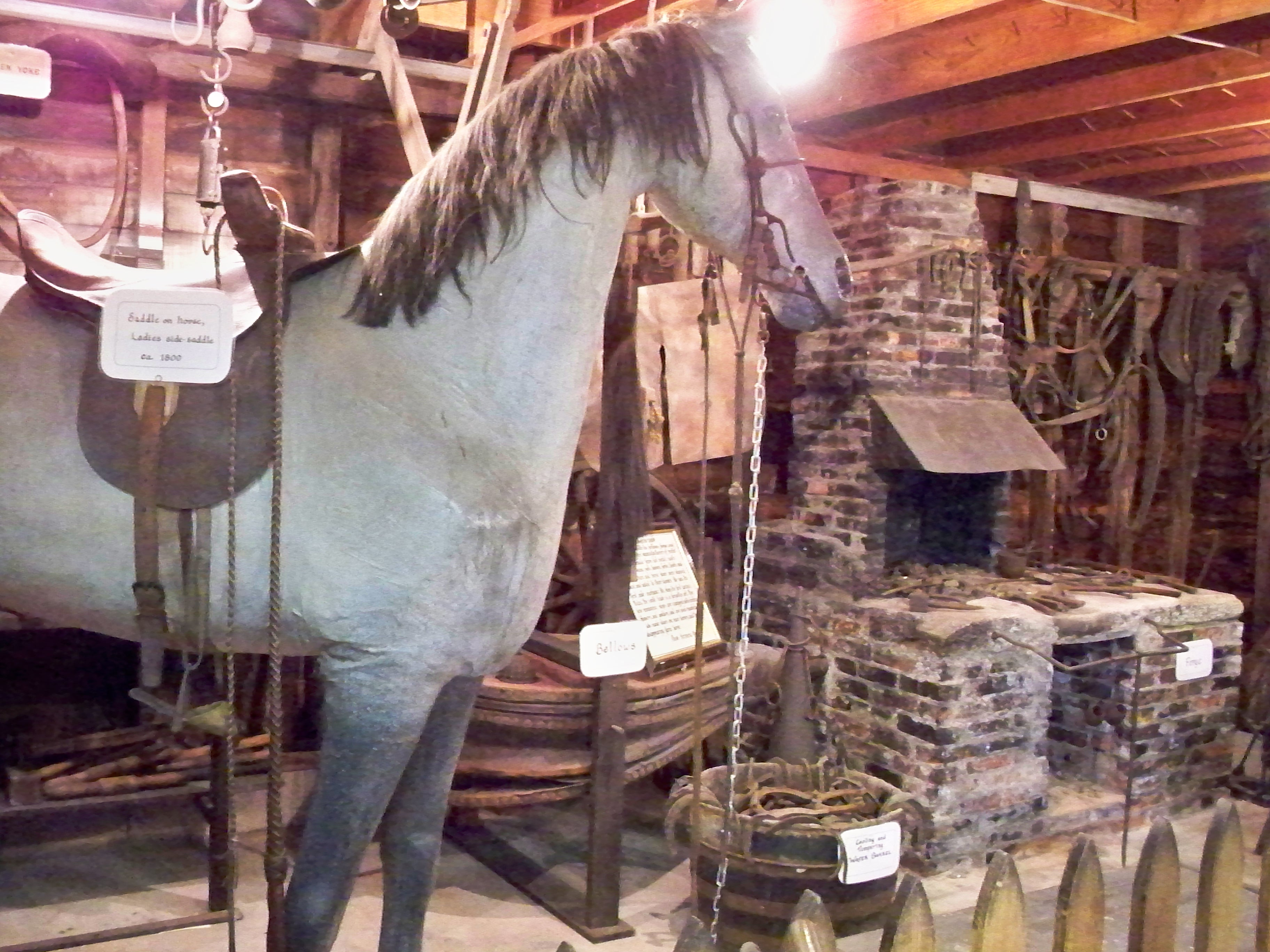 A blacksmith forge and bellows are in the background of a paper-mâché horse that would have sat in front of the shop to symbolize the blacksmith shop for any illiterate patrons.