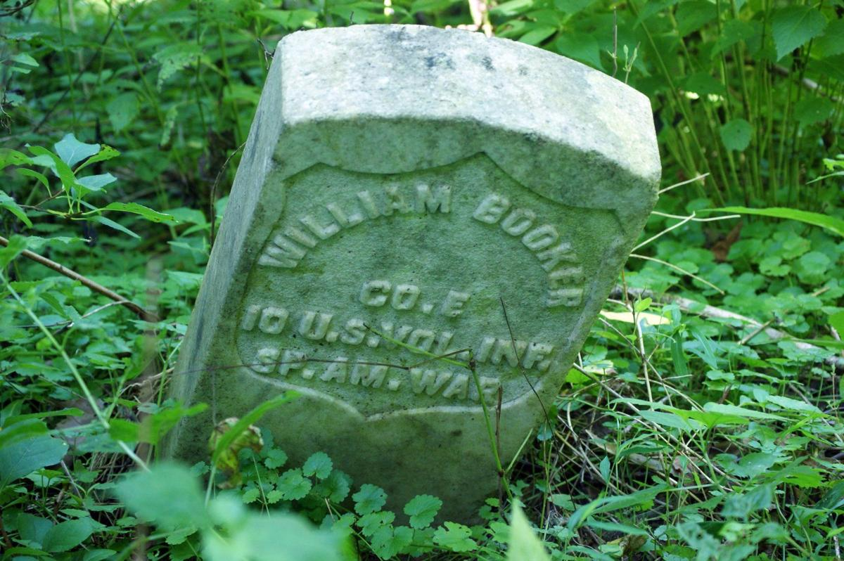 Headstone of Spanish-American War Veteran, William Booker, slumped over in the woods