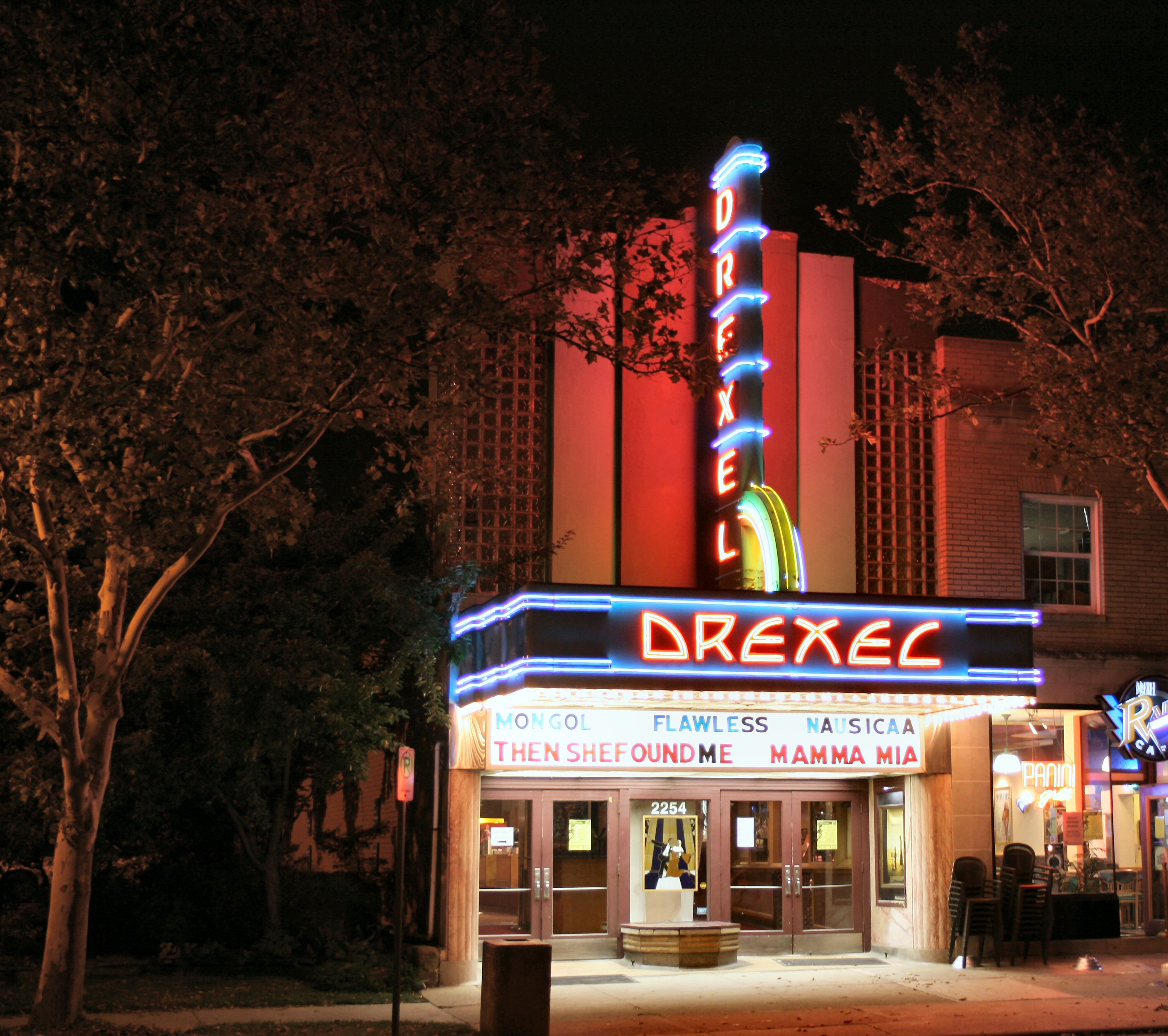 A view of the Drexel Theater's brightly-lit entrance.