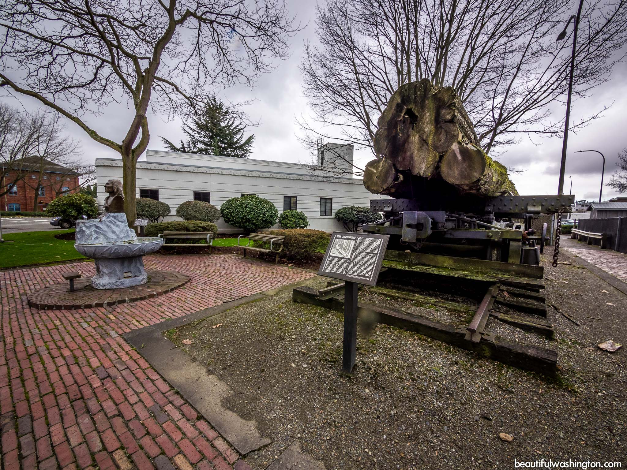 Behind the museum with a small garden, logging rail car and statue of Chief Seattle..