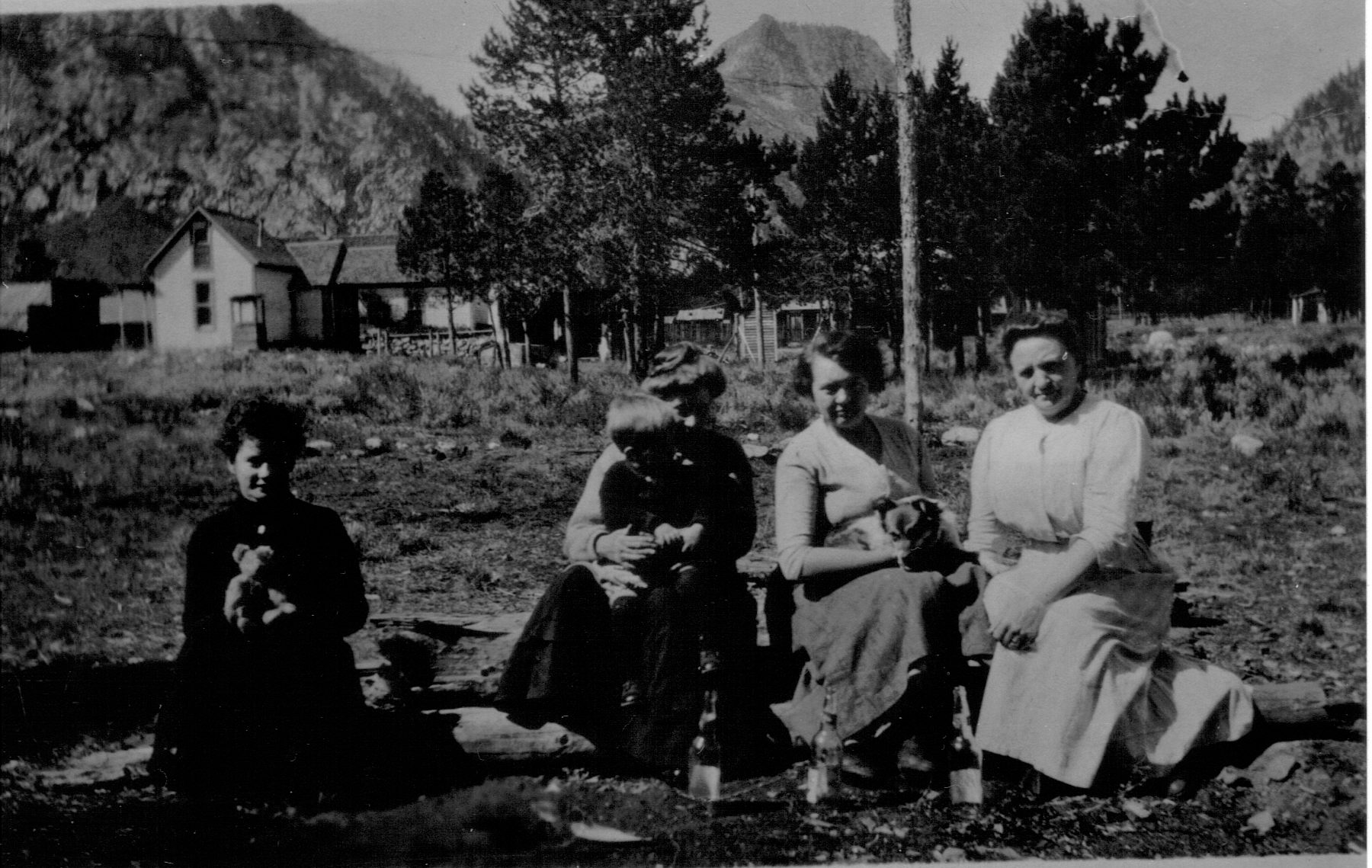 A black and white photo from 1915 featuring a group of women with a young child and a dog. One woman sits apart from the rest holding what looks like a teddy bear. Notice their long skirts and sleeves.