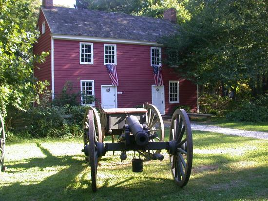 A canon sits in front of one of the buildings at the museum