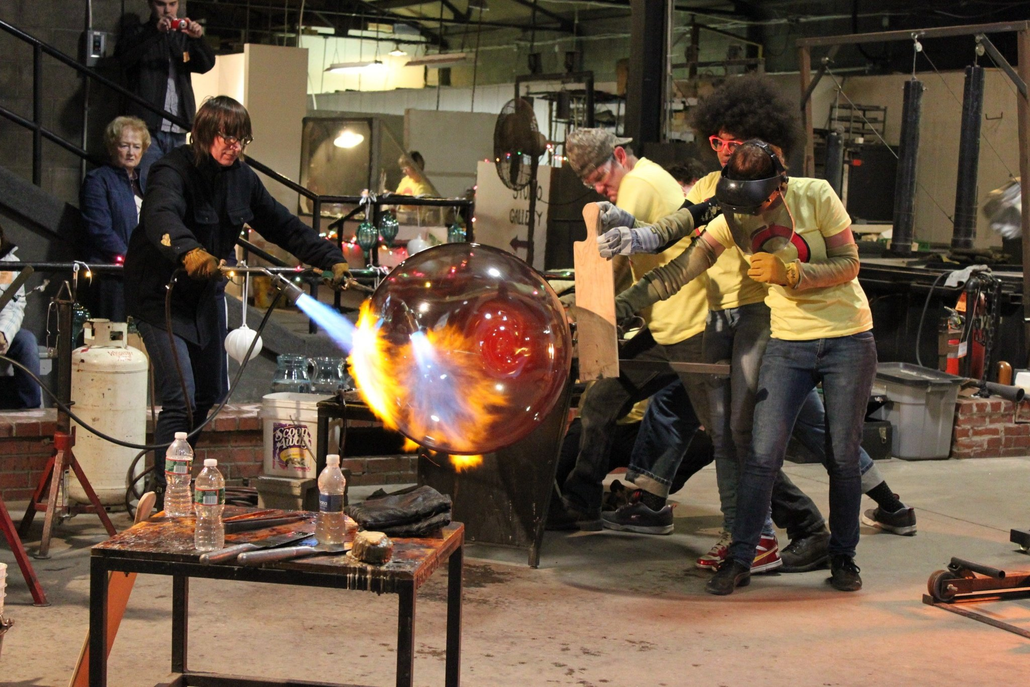 Artists making a large glass piece in the glass studio