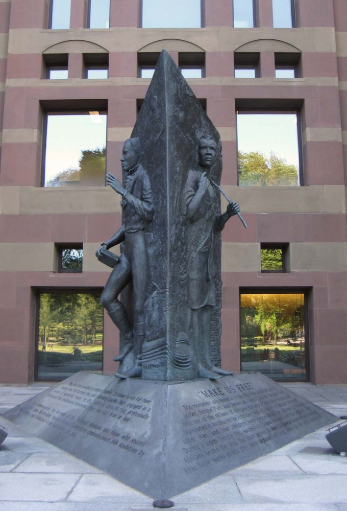 This monumnet was dedicated in 1992. This three-sided relief sculpture tells the story of Cinque's journey from freedom in Sierra Leone, to his capture and trial in the Americas, to his return to freedom in Africa.
