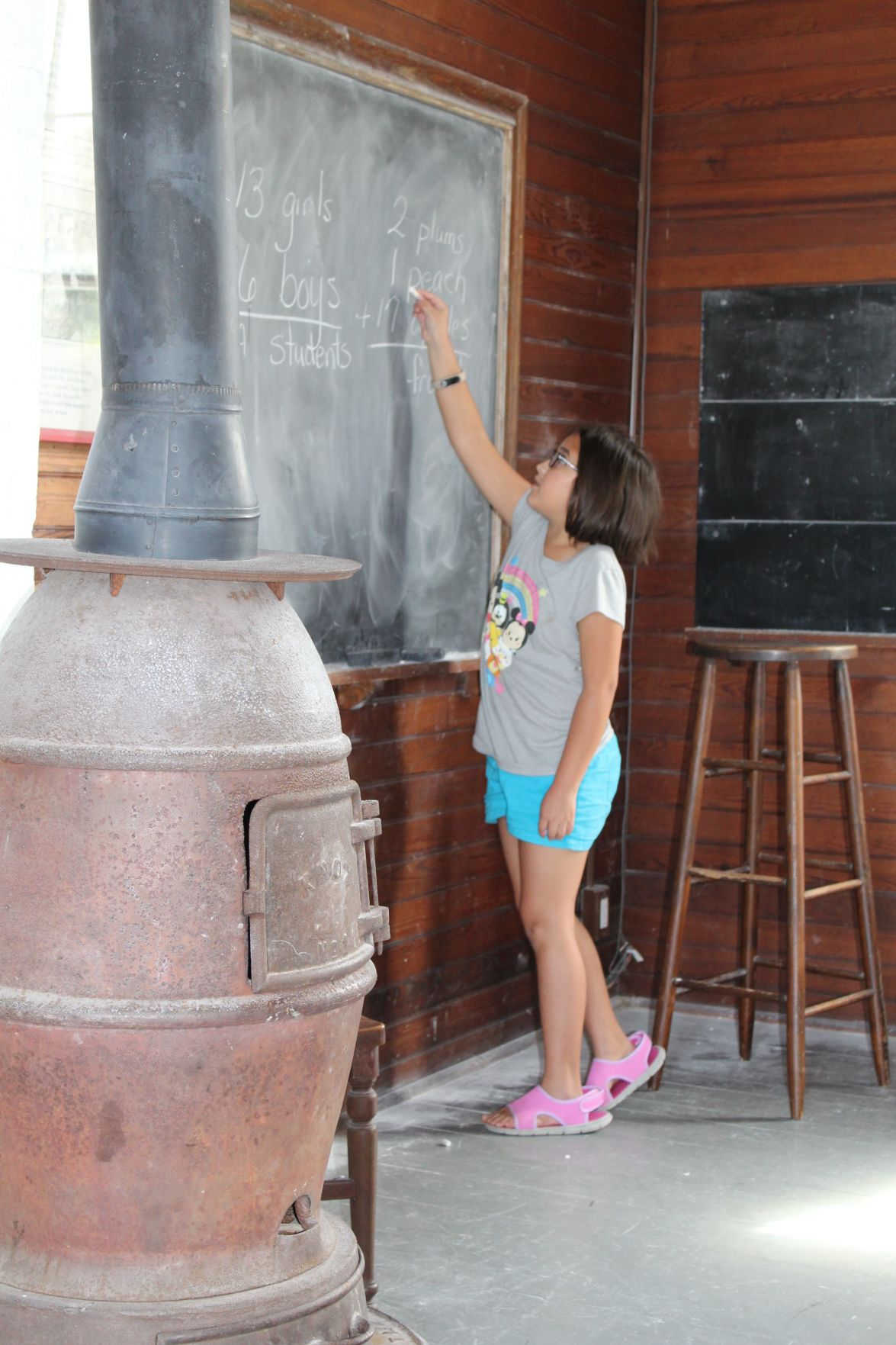 Student writing on board during schoolhouse lesson