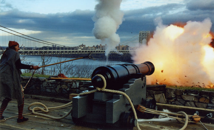 A canon is fired during a reenactment at the museum. The George Washington Bridge is in the background.