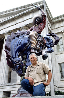 Creator of the Blue Mustang, Artist Luis Jiménez, posing with his work Vaquero.