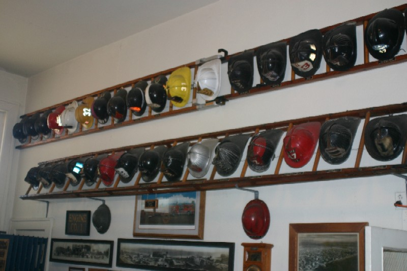 Vintage fire fighting helmets on display.