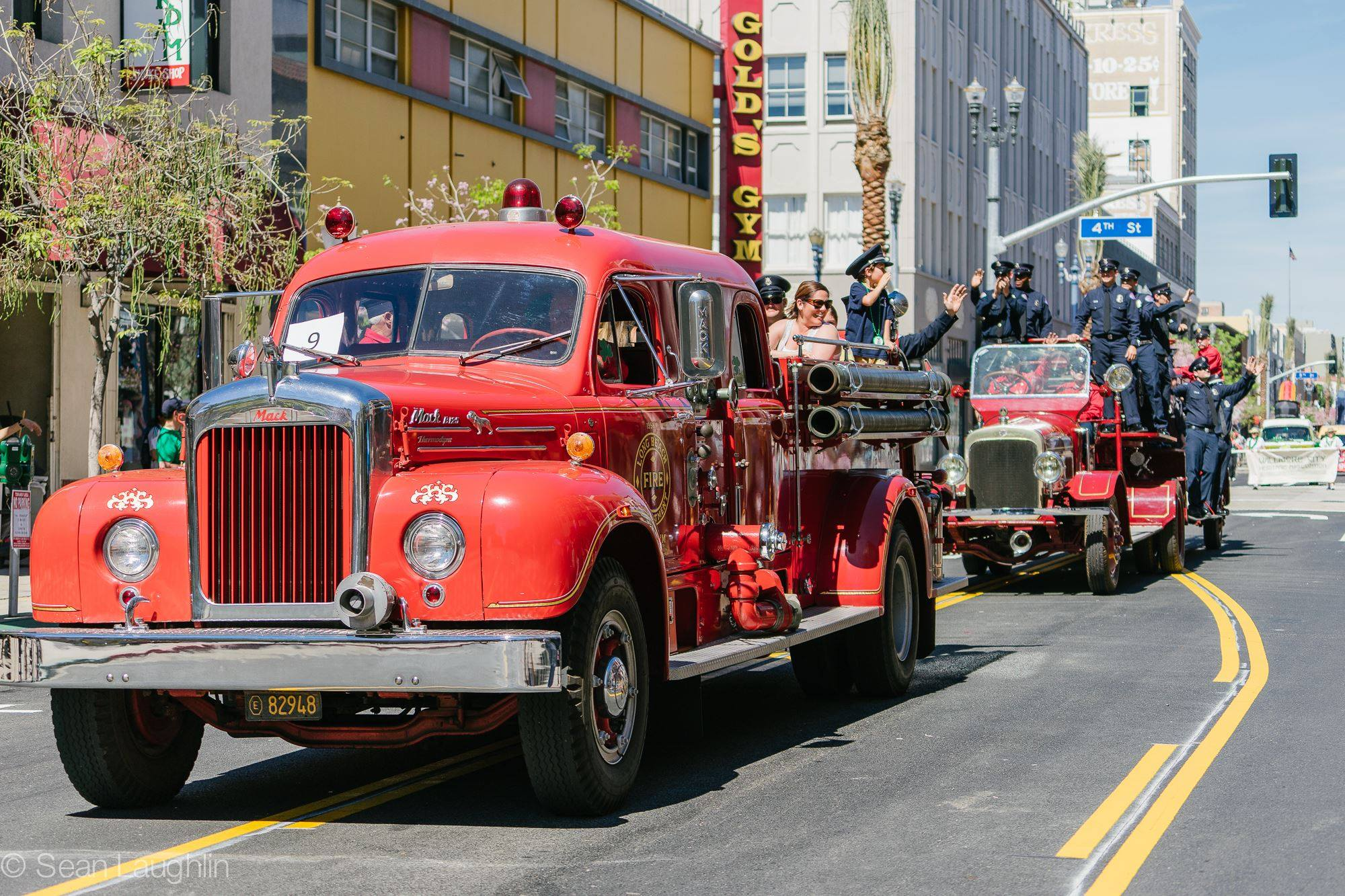 Firefighters and vintage vehicles participating in a local parade