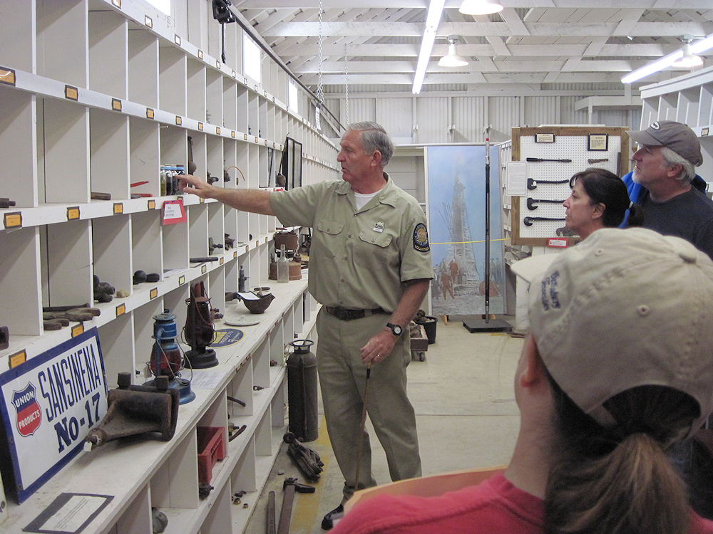 A ranger discussing the various oil industry artifacts to visitors.
