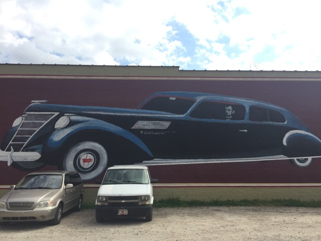 Present Day Mural of Abraham Lincoln driving a Lincoln on the side of the the Theatre