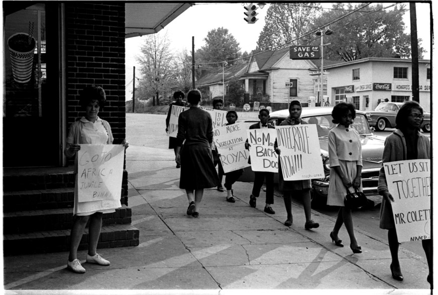 Protesters marching in front of parlor at a later protest in 1962. Photo from the Herald-Sun.